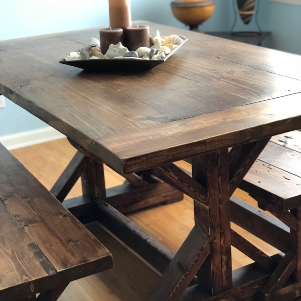 Farmhouse table sitting in room with sun coming through window.