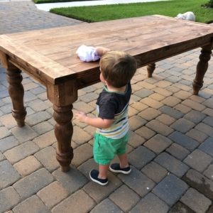 Little boy wiping off a Kathleen farmhouse style table
