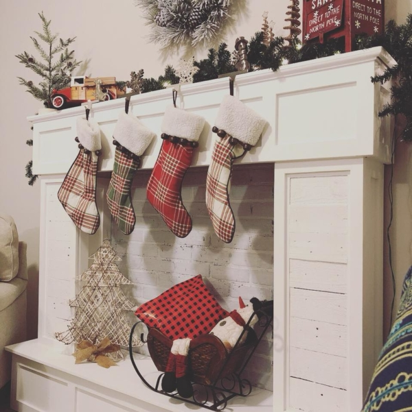 Faux Fireplace with stockings and Christmas decor sitting on top.